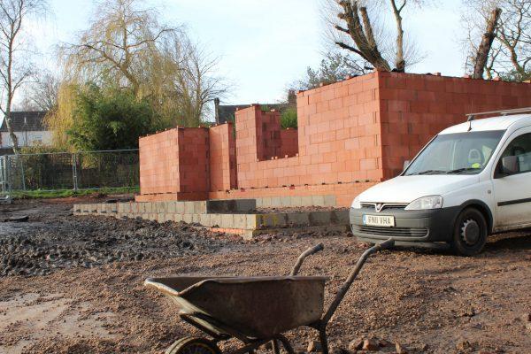 a red brick half built building by edgbaston reservoir